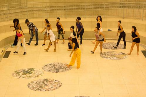 Organizadas em duas fileiras, as doze mulheres fazem o mesmo movimento, acompanhando a mulher de turbante que está à frente delas. Elas inclinam o tronco um pouco pra frente e para o lado, e apoiam um calcanhar no chão, enquanto o outro pé fica bem fixo no chão.