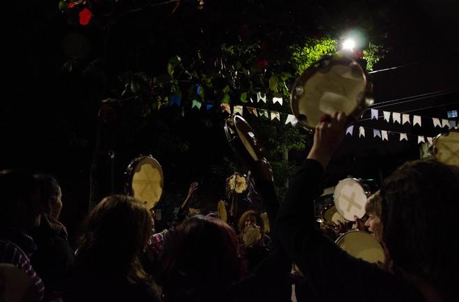 De costas, várias mulheres erguem seus pandeiros em uma das mãos. Ao fundo, a luz do poste ilumina as folhas pequenas de uma árvore grande.
