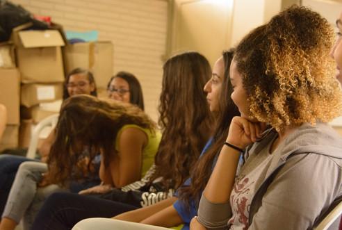 Seis garotas estão sentadas lado a lado, nas cadeiras de plástico branco. Uma delas, está de cabeça baixa com as mãos no rosto, e as outras garotas a observam, quase todas sorrindo. As adolescentes usam calça jeans e blusa de mangas curtas ou longas. A garota mais próxima tem cabelos cacheados e curtos, mais claros nas pontas. As outras meninas têm cabelos longos e castanhos.