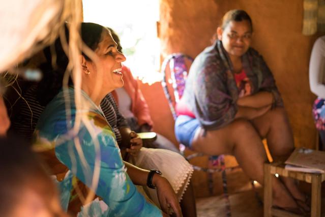Dentro da casa, uma mulher sorridente está sentada, em meio a outras mulheres. Mostrada de perfil, a mulher tem pele morena, cabelos escuros e presos, e usa blusa azul estampada. Ao fundo, uma moça a observa, com um sorriso sutil. A luz forte do Sol entra pela janela à esquerda.