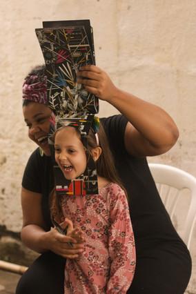 A menina de cabelos longos ri, enquanto encaixa seu rosto no buraco recortado em uma das páginas do livro ilustrado da primeira foto. Agachada atrás da menina e também sorrindo, Carol segura para cima o restante das páginas com a mão esquerda.