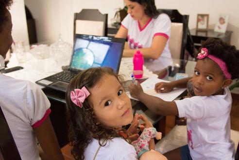 Na ponta da mesa e perto de suas mães, Isadora e Iasmim olham para a câmera. Isadora, de pé, segura no colo uma boneca bebê com roupa estampada. Sentada, Iasmim desenha em uma folha de papel branco. Rúbia e Silvânia estão sentadas frente a frente, cada uma de um lado da mesa. Rúbia olha para o laptop à frente, e Silvânia olha para baixo.