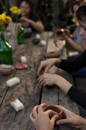 As mulheres modelam pequenas peças de argila, tocando-as delicadamente com as pontas dos dedos. A mulher mais próxima, da qual vemos só as mãos, pressiona as bordas de sua peça, que lembra um copo de boca larga.