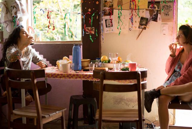 Sentadas à mesa, frente a frente, duas mulheres lancham. A mulher á esquerda tem cabelos longos e ondulados, e está vestida com blusa estampada e calça escura. Ela está com os pés descalços sobre a cadeira, e toma café em um copo. A mulher da direita tem cabelos curtos e castanhos, usa casaco rosa sobre vestido azul, e botas. Ela está com as pernas cruzadas e come algo. Sobre a toalha florida da mesa, entre outras coisas, há copos, uma garrafa térmica, pães e uma vasilha com frutas. Acima da mesa, está esticado um fio, onde estão penduradas algumas fitas brilhantes. Ao fundo, na parede, há um mural com textos e desenhos. Ao lado, a janela aberta deixa entrar a luz do Sol.