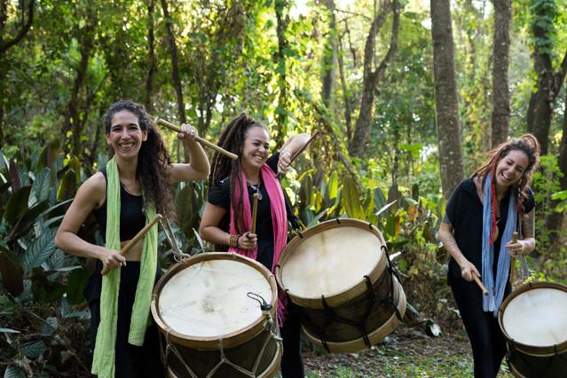Ainda em meio a vegetação, as mulheres, agora de pé,  sorriem e tocam tambores mineiros iguais, usando baquetas de madeira. Cada uma segura seu tambor por uma corda no ombro. Isabela e Poliana erguem bastante um de seus braços.