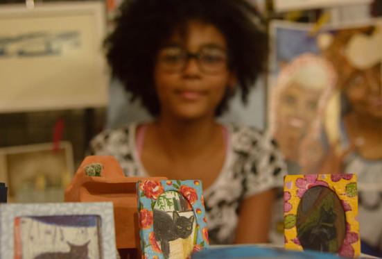 Sobre uma mesa estão, em destaque, 3 pequenos porta-retratos, com desenhos de gatos pretos. Os porta-retratos são recobertos com tecidos florais e coloridos. No fundo, que está desfocado, há uma moça negra, de cabelos crespos, curtos e escuros. Ela usa blusa estampada preta e branca, óculos grandes, e esboça um sorriso. Atrás dela, há alguns desenhos e gravuras.