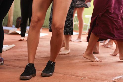 No chão de cimento marrom, vemos várias pernas que caminham pelo espaço. Há pernas morenas e calçadas com tênis preto, e outros quatro pares de pernas descalças,  vestidos com calça preta, calça curta e estampada, mini-saia, e saia longa cor de vinho. Ainda vemos os pés descalços de mais duas pessoas, e um tênis colorido, que espreita à esquerda.