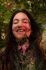 foto de Lina, mostrada do peito para cima. Ela tem pele clara, cabelos castanhos, compridos e ondulados.  Sorri, olhando para frente. Sobreposta a foto, está o desenho de uma flor e uma folha.