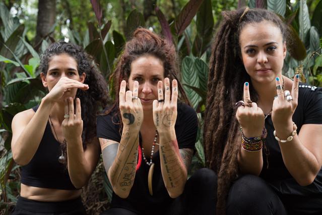 Poliana, Chaya e Isabela estão lado a lado, fazendo diferentes gestos com as mãos. Todas têm pele clara e usam roupas pretas. Cada uma mantém os braços dobrados e paralelos à frente do peito, e as palmas das mãos voltadas para si. Poliana, que tem cabelos escuros e ondulados, exibe três dedos de uma mão, enquanto a outra mão fica acima desses dedos, como se os protegesse. Chaya, que tem dreads avermelhados, mostra três dedos com uma mão e dois com a outra. Ela tem os braços tatuados. Isabela, que tem dreads castanhos e muito longos, mostra o dedo do meio de uma mão e o indicador e o anelar da outra. Ela tem unhas pintadas de azul, e diversas pulseiras. Ao fundo, estão plantas com folhagens grandes.