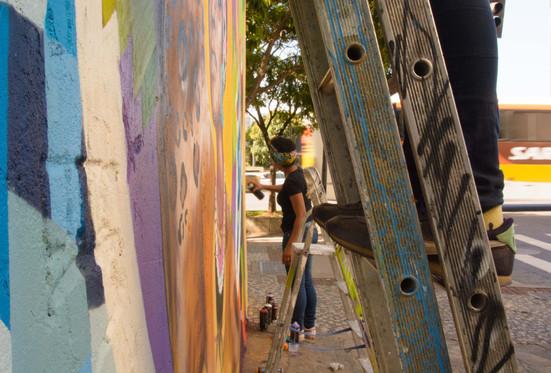 Por debaixo da escada onde está Krol, vemos Nica na calçada, pintando o muro com spray. Só vemos os tênis e a calça preta de Krol. A escada onde ela sobe está cheia de manchas e riscos de tinta. Ao fundo, um ônibus passa na rua.