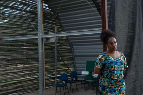 Débora está de pé e com os braços para trás, ao lado de uma estrutura semi-aberta, dentro da qual estão quatro carteiras escolares, e um pequeno quadro negro no chão.