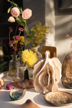Sobre uma mesa banhada pela luz suave do Sol, estão peças de cerâmica, cristais, uma garrafa de vidro com rosas e um vaso com um crisântemo amarelo. Em destaque, está uma peça bege com pequenas manchas marrons, que remete a uma vulva. No centro dela, há uma fenda vertical cercada pelos pequenos lábios, duas abas semicirculares que se unem na parte baixo de forma mais arredondada e na parte de cima, de forma mais afunilada. Ao lado de cada lábio, há mais três abas maiores. Ao lado dessa peça, há uma pequena cumbuca, e um vaso e um prato em cerâmica, decorados com linhas finas e irregulares marrons, que lembram veios de rios.