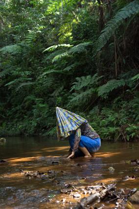 Uma pessoa está agachada em um riacho largo e raso, tocando na água com os dedos. Ela usa calça azul e camisa estampada. Tem a cabeça envolta por um tecido azul e amarelo, como se fosse de um guarda-chuvas semi-fechado.  O riacho de águas marrons é margeado por samambaias e outras plantas verdes.