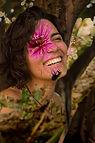 foto de Catarina, mostrada de peito para cima. Ela tem pele clara, cabelos curtos e castanhos. Sorri, com os olhos semicerrados. Sobreposta a foto, na altura do olho de Catarina, está o desenho de uma flor cor de rosa.