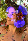 foto de Renata, mostrada do peito para cima. Ela tem pele clara, cabelos claros, compridos e ondulados. Sorri, olhando para a esquerda.  Sobreposta a foto, na está o desenho de uma flor roxa.