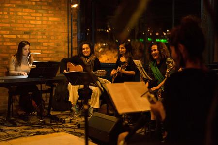 Cinco mulheres jovens, de pele clara, e vestidas com roupas de frio estão sentadas em um semicírculo. Todas têm à sua frente partituras colocadas em tripés. Da esquerda para o centro, três mulheres tocam seus respectivos instrumentos: uma tecladista de cabelos lisos e longos, uma violonista de cabelos cacheados, e uma cavaquinhista de cabelos longos, divididos na lateral. À direita, uma moça com uma echarpe verde, que é muito parecida com a violonista,  segura no colo um instrumento inidentificável. Mais à direita, está uma mulher morena de costas. O local tem chão de pedras portuguesas, uma parede de tijolos aparentes e janelas envidraçadas, que permitem ver a noite escura e luzes da cidade no exterior.