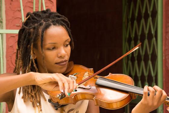 Foto próxima de Nath, tocando o violino. Ela apóia a base do pequeno instrumento entre o queixo e o ombro esquerdo. Com a mão esquerda, ela pressiona as cordas no braço do violino e, com a mão direita, desliza o arco de maneira perpendicular sobre as cordas. Os dreads nos cabelos de Nath são mais claros nas pontas. Ela tem um piercing em forma de argola no meio do nariz, e usa um longo colar amarelo.