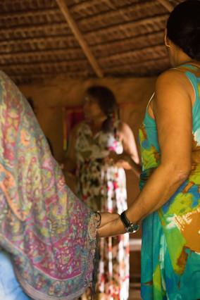 Por detrás de duas mulheres de mãos dadas, vemos outra mulher ao fundo, que também segura as mãos de duas pessoas, cada uma de um lado. As três mulheres mostradas estão de pé e usam roupas com estampas coloridas, em estilos diferentes. O círculo de mulheres está dentro da casa circular.