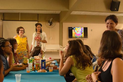 Na mesma sala, Graziane e Adriana, de pé, observam as garotas lanchando. Elas estão sentadas em torno de uma mesa de toalha azul, com caixas de suco, bolos e  sacos de pão. Outra mulher sorridente, de pele clara e cabelos grisalhos presos, também observa as garotas. A TV ao fundo agora exibe um desenho colorido.