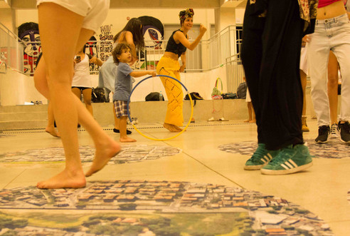 Em meio a uma profusão de pernas de mulheres dançando, uma criança segura um bambolê azul e amarelo, e observa o movimento. A criança tem pele morena e cabelos cacheados. Está vestida com blusa azul, bermuda xadrez, e está descalça. Ela apóia o bambolê no chão e o firma em pé com uma das mãos. Atrás da criança, duas mulheres estão quase na mesma posição, inclinando o tronco um pouco pra frente. Uma delas, vestida com calça amarela, blusa preta e turbante na cabeça, sorri e ergue o punho cerrado na altura do rosto.