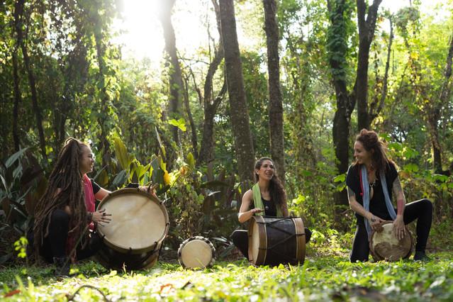 Durante o dia, em meio a grama, arbustos e árvores, as três mulheres sorridentes estão agachadas, tocando tambores de tamanhos diferentes. Isabela, que usa uma echarpe rosa, bate a palma da mão na superfície de um grande tambor mineiro com cordas amarradas nas laterais. Poliana, que usa uma echarpe verde, deixa a mão erguida acima de um tambor mineiro menor, que está deitado à frente dela. Chaya, que usa uma echarpe azul, apóia um dos pés no chão e bate as mãos na superfície de um tambor pequeno.