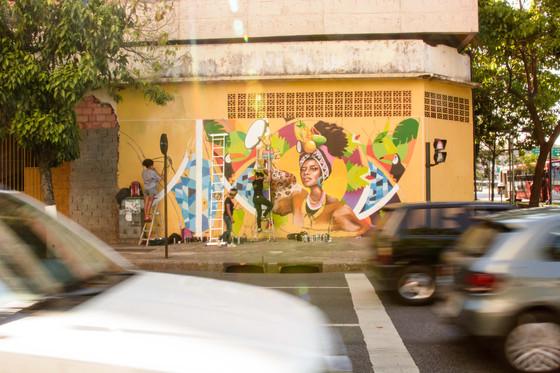 Ao fundo, depois dos carros em trânsito na rua, vê-se todo o muro laranja, na parte de baixo de um prédio de esquina. Krol está em uma escada bem no meio do muro, Nica está ao lado dela na calçada, e Lidia está à esquerda, numa escada baixa, esboçando os últimos traços do desenho com linhas pretas. A parte já pronta do grafite mostra uma mulher negra, segurando um pandeiro com a mão direita. Ela usa um turbante na cabeça, cheio de frutas tropicais, como coco, manga e abacaxi. Também usa argolas azuis nas orelhas, colar de contas, e uma roupa marrom com mangas bufantes, estampada com manchas de onça pintada. A redor da mulher, estão tucanos, folhas verdes e outras frutas.