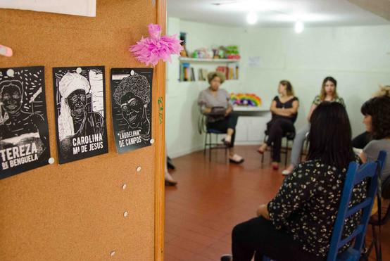 Próximo ao quadro de cortiça com as xilogravuras, vemos a sala com a roda de mulheres à direita.