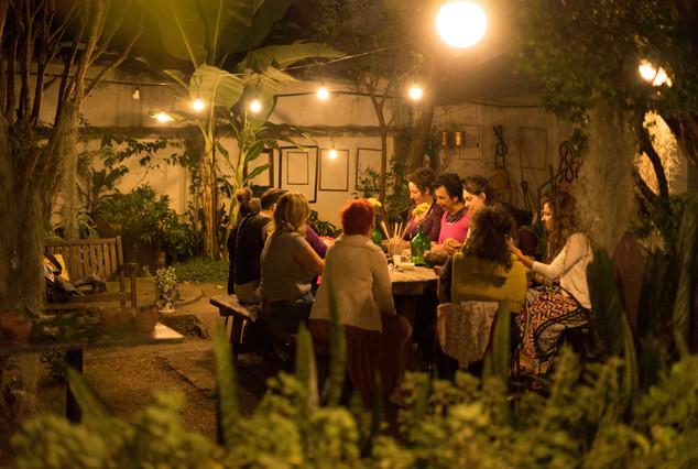 Já à noite, há dez mulheres sentadas à mesa, que fica em um grande jardim. O jardim tem árvores, plantas diversas e alguns bancos de madeira. Entre as árvores, está esticado um fio com lâmpadas, que iluminam a mesa. Na parede branca do fundo, estão penduradas algumas molduras de diferentes cores e tamanhos.