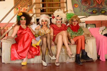 Quatro mulheres estão sentadas em um sofá bege, lado a lado e de pernas cruzadas. Da esquerda para a direita estão: uma mulher com um vestido de festa vermelho; outra de vestido azul com uma peruca branca; outra de vestido vermelho e cinto amarelo, com o nariz pintado de vermelho e a boca pintada de branco; e uma com peruca loira, boá vermelho, vestido verde e cintilante, meia calça laranja e botas pretas. Atrás do sofá, vê-se dois quadros de tecido pendurados na parede, e o corrimão de uma escada baixa.