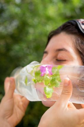 De olhos fechados, uma pessoa de pele clara e cabelos castanhos encosta o nariz e a boca em uma embalagem plástica e transparente, contendo uma flor roxa e folhas verdes. Só vemos as mãos da pessoa que segura a embalagem.