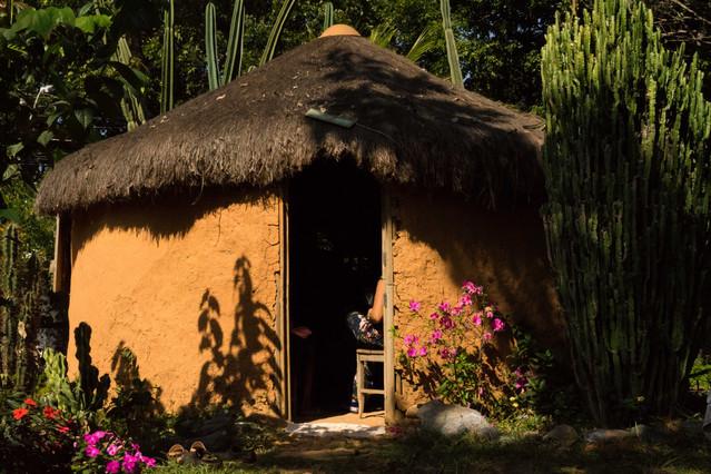 Do lado de fora de uma casa com a porta aberta, vemos algumas pessoas sentadas do lado de dentro. A casa é pequena, circular, coberta com telhado de sapê e revestida com tinta de terra laranja, que confere às paredes um aspecto áspero e craquelado. À frente da casa, há um jardim com cactus de diferentes tipos e tamanhos, e flores vermelhas e cor de rosa. O sol forte ilumina a casa e o jardim.