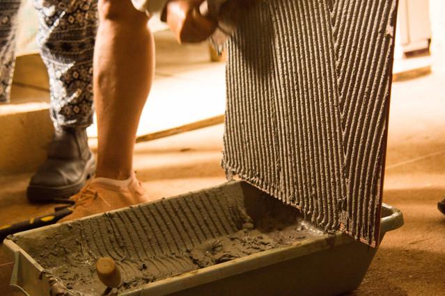Detalhe da aplicação de argamassa diretamente no verso de uma placa de cerâmica. A placa é apoiada verticalmente sobre a bandeja em que se mistura a argamassa.