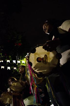 De baixo, vemos quatro mulheres de pé e lado a lado, tocando pandeiros. Através da pele esticada de cada instrumento, vemos a silhueta da mão que o toca. Em um dos pandeiros, há o desenho de uma mulher negra e o nome Cumbuca da Gil. Acima das mulheres, dois varais com bandeirinhas brancas se destacam contra o céu escuro da noite.