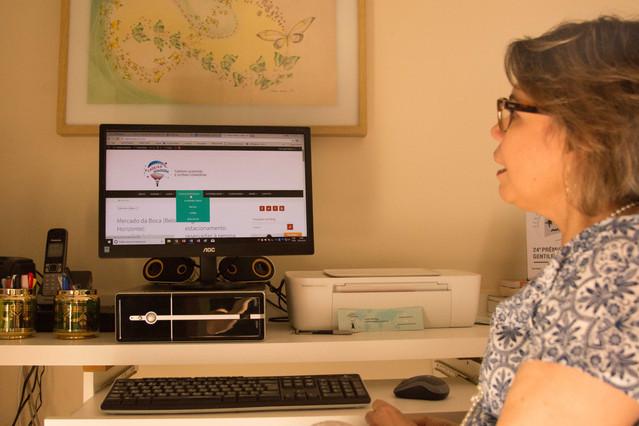 Laura está de frente para um computador, cuja tela exibe o site do Cadeira voadora. Na mesa branca onde ele está, também há um telefone, duas latinhas com canetas, e uma impressora. Na prateleira de baixo, estão o teclado e o mouse. Na parede do fundo, está pendurado um quadro com o desenho de uma borboleta grande, seguida por borboletas verdes e menores.