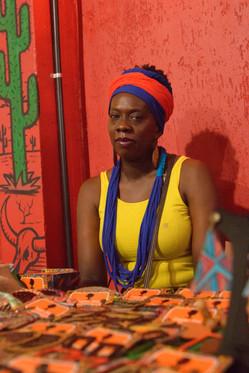 Uma mulher está sentada atrás de uma mesa cheia de cartelas com bijuterias. A mulher é negra, usa turbante azul e laranja, brincos grandes, um colar de contas azuis com várias voltas, e uma regata amarela. A parede ao fundo é laranja e tem, à esquerda , o desenho de um cactus verde, ao lado do crânio de um boi com chifres.