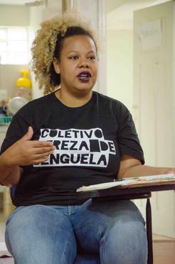 Renata Aline fala e gesticula, sentada em uma carteira escolar. Ela é negra e tem cabelos cacheados com pontas loiras, que estão presos em um rabo alto. Renata usa batom roxo, veste camiseta preta com o nome do Coletivo, e calça jeans. Sobre a prancheta da carteira, está um caderno.