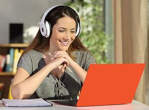 Happy student looking at orange laptop.j