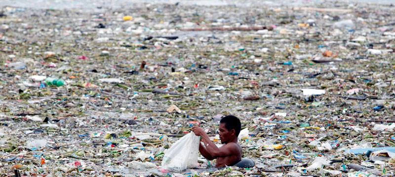 Dieses Bild zeigt einen Mann der durch ein Gewässer geht, dass bedeckt wird von einer großen Lache an Abfällen, überwiegend schwimmendem Plastik.