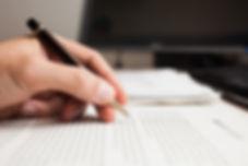 Mão segura uma caneta em cima de texto