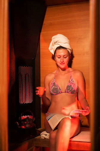 girl in an infrared sauna is drinking te