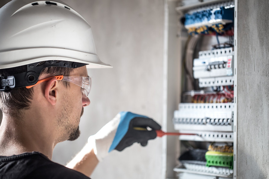 man-electrical-technician-working-switchboard-with-fuses-installation-connection-electrica