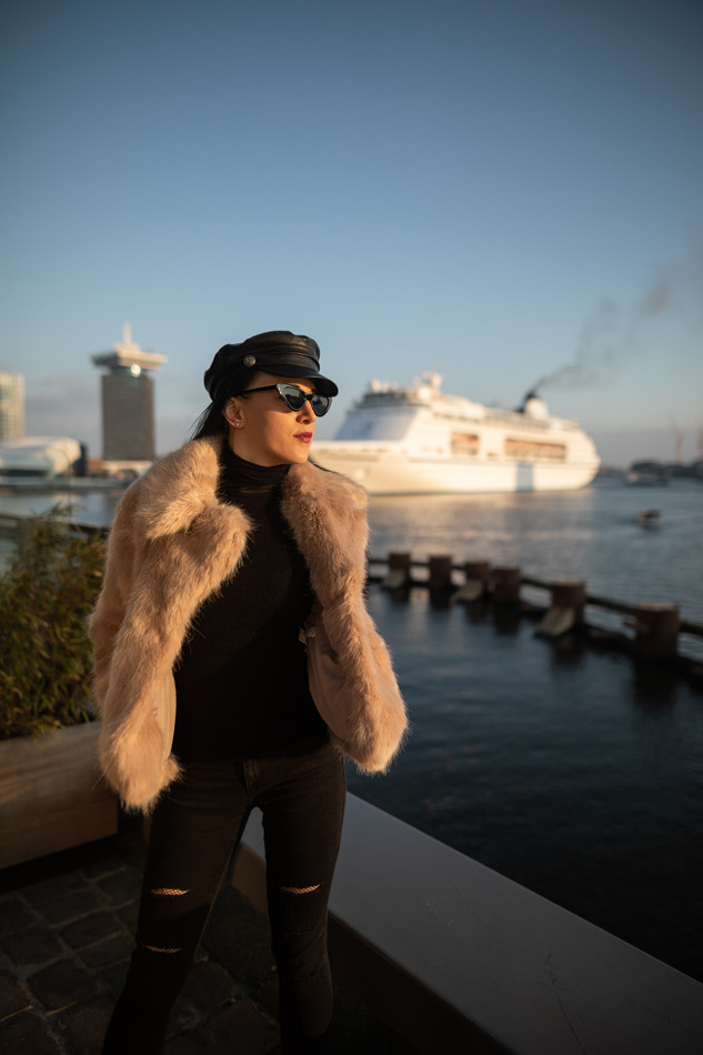 A girl in a hat and faux fur with ship cruise in the background in Amsterdam