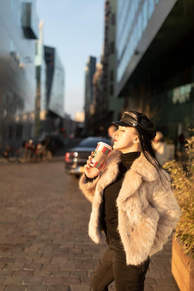 Beautiful girl drinking takeaway Sturbucks coffee wearing faux fur