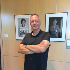 Andy Allen standing in front of two of his portraits. The ongoing series is of cancer patients. The portraits display the vitality and energy of patients - allowing the cancer therapy to be in the background.