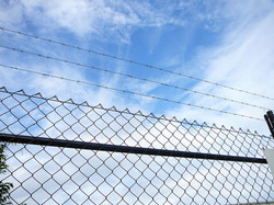 Chainwire fence with barbed wire
