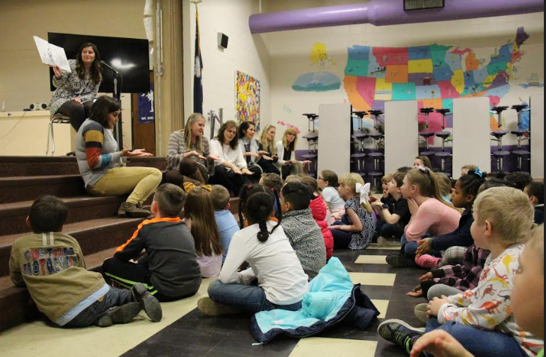 """Samantha Kennedy, the Instructional Coordinator for B-L Primary School, reads aloud the book """"We're Going on a Bear Hunt"""" on Thursday, March 7th as part of the school's family Literacy Night. Members of the school's literacy team are seen acting out parts of the book while students listen intently."""