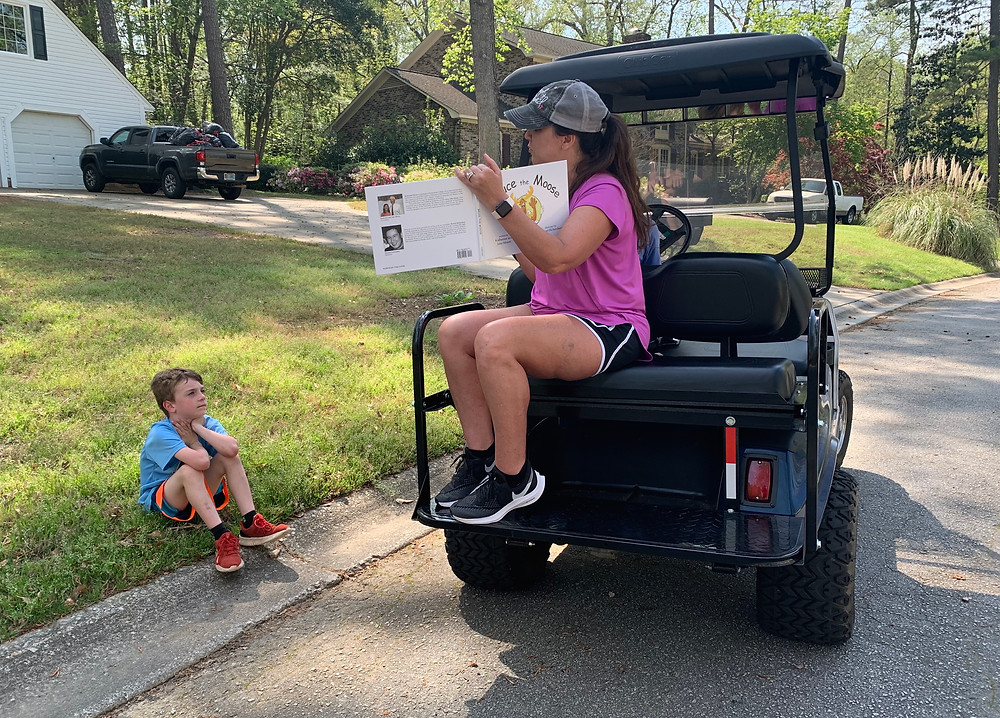 "Melanie Thornton reads to Quintin Ray, one of her Riverbank Elementary students. Thornton's ""rolling reading room"" goes out into her local neighborhoods to read books in what she calls her ""outdoor classroom."""