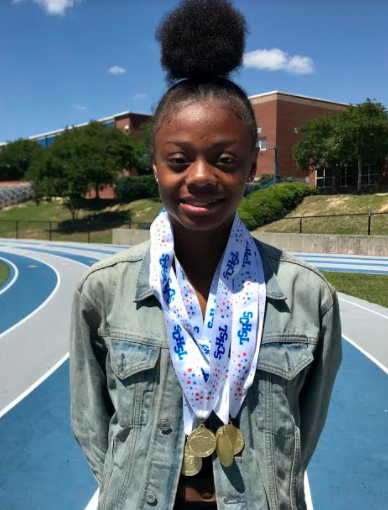 Jayla Jamison poses recently on Airport High's track with some of the medals she won at this spring's state championships.