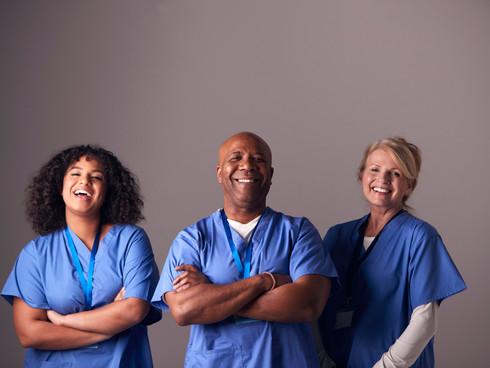 Studio Portrait Of Three Members Of Surgical Team Wearing Scrubs Standing Against Grey Background.jpg