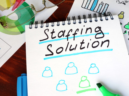Notepad with staffing solutions on a woo